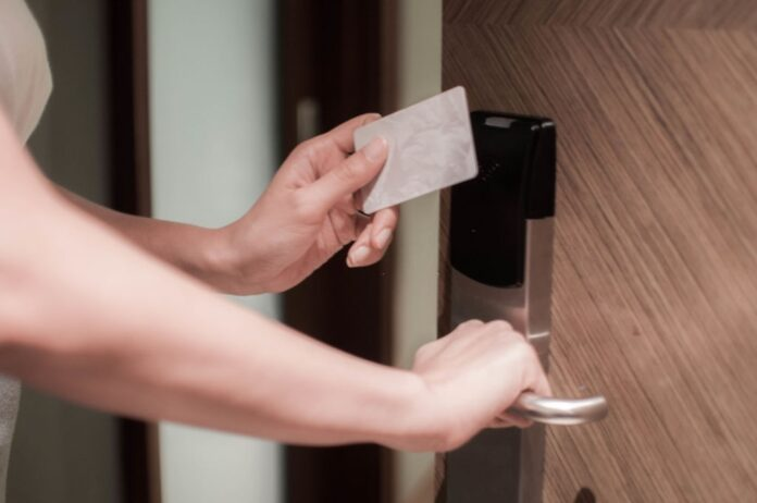 A close-up of a young woman is opening a door using a card key